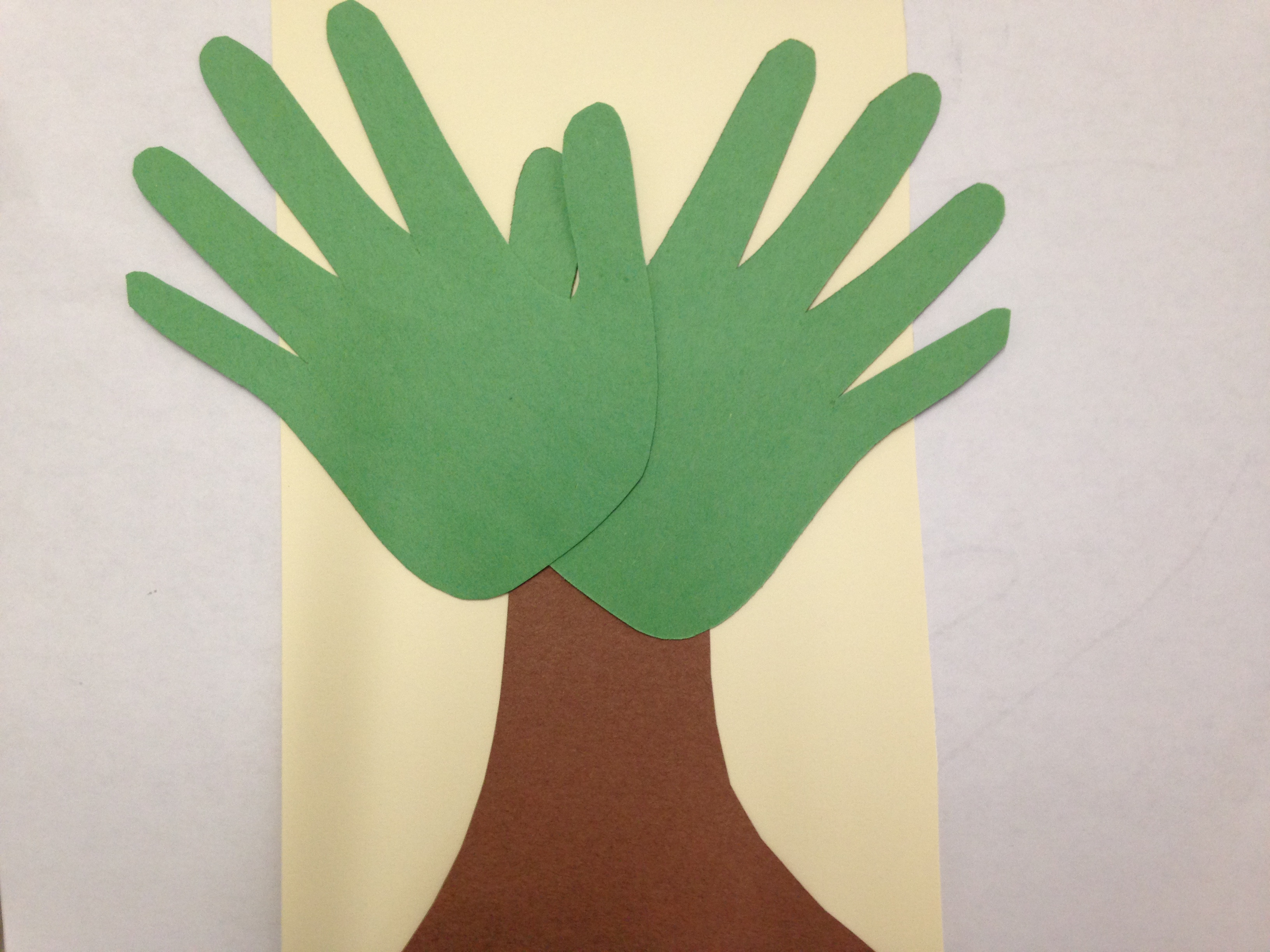 Construction paper hands glued to tree trunk cut out to make a tree